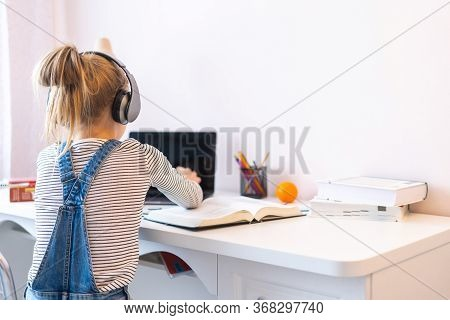 Portrait Of Teenage Girl Learning Online With Headphones And Laptop Taking Notes In A Notebook Sitti