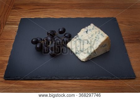 Stilton Blue Cheese With Sable Grapes On A Piece Of Grey Slate