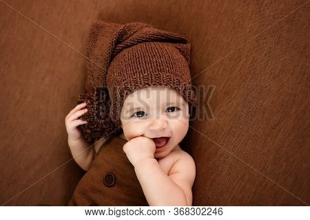 Cute Newborn Baby On A Brown Blanket. Smiling Baby On A Dark Background. Closeup Portrait Of Newborn