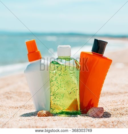Bottles Of Sun Protection Lotion, Aloe Soothing Gel From Sun Burn, Seashells In Sand On The Beach Wi