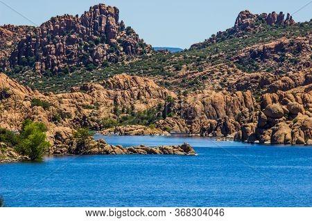Bright Blue Lake With Unique Rock Formation Shoreline