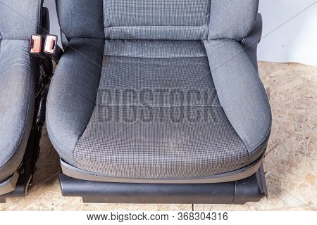 A Close-up Of A Pair Of Front Seats Of A Car Covered In Gray Fabric With A Curly Pattern With Plasti
