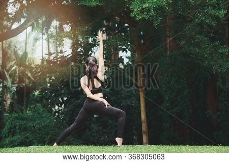 Asian Woman Practicing Yoga In Warrior Pose (virabhadrasana) On The Mat In Outdoor Park.