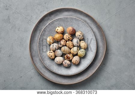 Quail Eggs On Gray Ceramic Plate On Grey Concrete Rough Background. Little Spotted Eggs On Uneven Ma