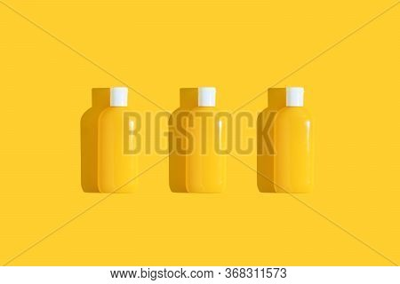 Thee Yellow Tube Of Sunscreen On A Bright Yellow Background With Hard Shadow. Sun Protection In The