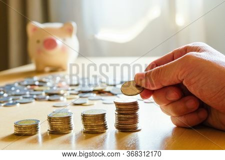Selective Focus Asian Men Hand Put Coin Into Stack With Piggy Bank On Background. Saving Plan For Re