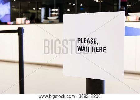 Please Wait Here And Keep Distance  Sign In Front Of Purchase Counter In Department Store For People