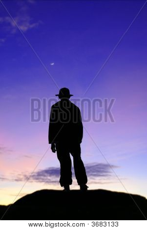 Male Silhouette On Mountain In Twilight