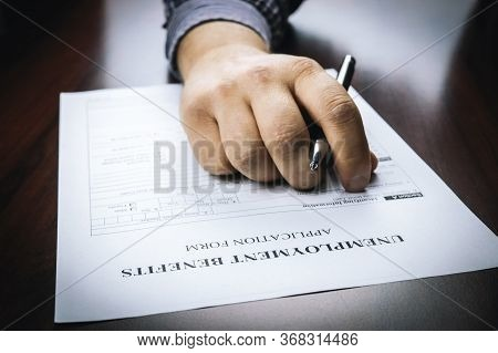 Close-up Of A Person's Hand Filing Social Security Benefits Application Form.  Concept Of Covid-19 C