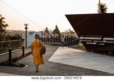 Woman In Yellow Sundress Walking By City Travel Landmark
