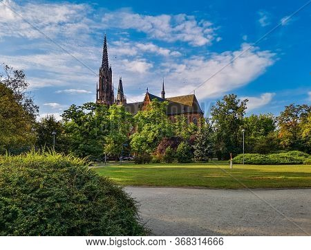 Green Park Of Saint Edith Stein With Old Cathedral In Background