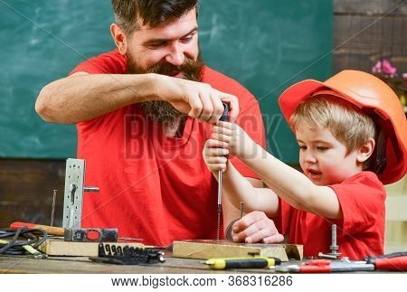 Boy, Child Busy In Protective Helmet Learning To Use Screwdriver With Dad. Father, Parent With Beard