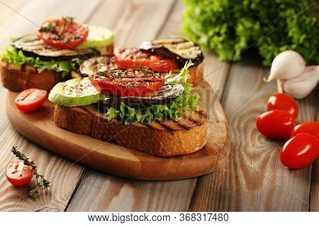 Vegetarian Hot Sandwich Made From Grilled Bread, Grilled Eggplant, Zucchini And Tomatoes, With Green