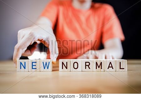 Woman\'s Hand Putting Wooden Cubes With Concept New Or Next Normal. New Normal Life After Covid Cris