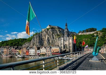 Picturesque Dinant town, Dinant Citadel and Collegiate Church of Notre Dame de Dinant and Charles de Gaulle bridge with saxophones as Dinant is hometown of saxophone inventor and flags. Namur, Blegium