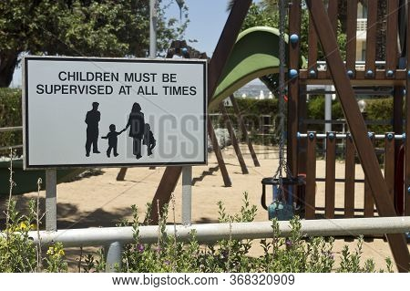 Sign Board Children Must Be Supervised At All Times On A Playground Fence In Sunlight