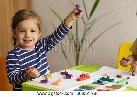 Little Girl Playing With Plasticine On A Table In The Nursery Sitting. Plasticine Molding. Developme