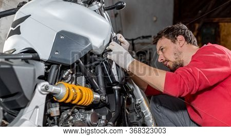 Mechanic Repairman Doing Maintenance Or Repairing, Fixing On The Motorcycle, Motorbike, Service Cent