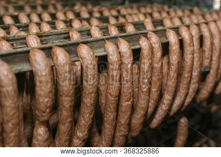 Sausage Production Line. Sausage On The Counter For The Smokehouse. Industrial Manufacture Of Sausag