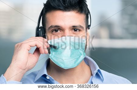 Masked man using his mic headset for a remote call