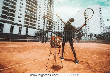 Wide-angle View From Behind Of A Young Slim Biracial Woman Aiming A Blow Before Hit A Tennis Ball Du