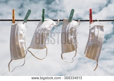 Medical Face Masks Hanging On A Clothesline With Clothespins In Sky Background.