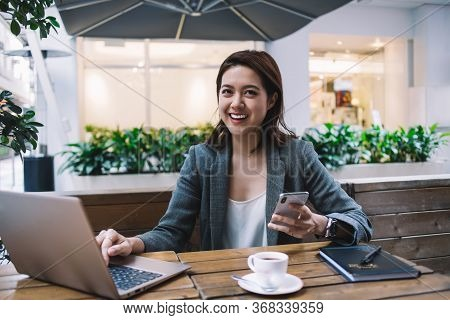 Cheerful Young Businesswoman Browsing Mobile While Using Laptop At Cafe
