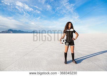 Outdoor portrait of a confident young mixed race female soccer player. Photo taken at the Bonneville Salt Flats. Women's soccer concept photo
