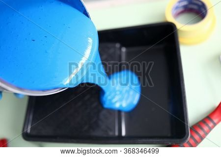 Top View Of Person Pouring Blue Paint For Painting Wall In Apartment. Black Plastic Container For Re