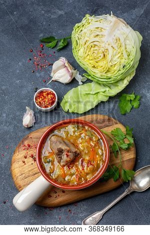 Soup With Fresh Cabbage, Vegetables And Oxtail In A Ceramic Bowl Is Served On An Old Wooden Board. T