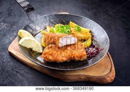 Traditional deep fried veal steak with roast potatoes and cranberry sauce offered as closeup in a rustic old wrought iron skillet on a wooden board