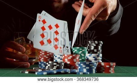 Poker player throwing cards. Concept of hazard gaming, poker chips on table