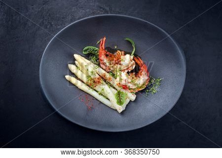 Traditional barbecue spiny lobster tail sliced and offered with white asparagus and lettuce as top view on a modern design plate