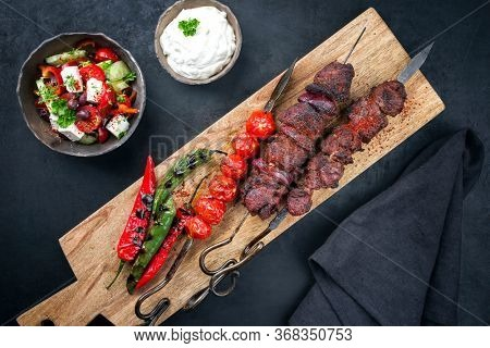 Traditional Greek souvlaki barbecue skewer with farmer salad and tzatziki as top view on a wooden cutting board