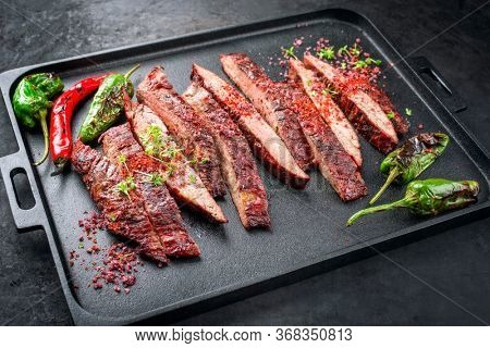 Traditional barbecue sliced dry aged wagyu flank steak offered with chili and paprika as closeup on a modern design cast iron tray