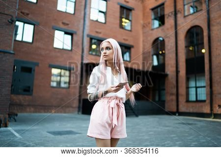 Attractive Caucasian Teenager With Tattooed Hand Pondering On Information From Smartphone Gadget