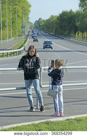 Little Girls Take Pictures Of Each Other Near The Highway. Sisters Take A Photo For Memory. Children