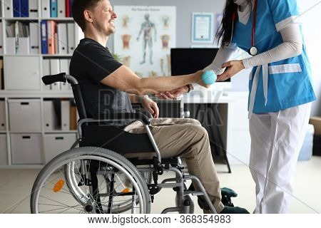 Doctor Helps Man On Wheelchair Hold Dumbbell. Strengthening Human Parts, Ability To Part With Wheelc