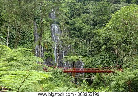 Red Bridge Over The River Near A Waterfall In The Mountains In T