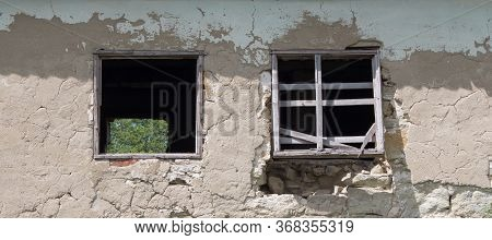 Wall Of Old Blocks With A Damaged Wooden Window Without Glass. Vintage Village Building