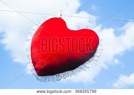 Red Heart Shaped Cushion (pillow) Hanged On The Clothes Line And Fastened By The Clothes Peg Against