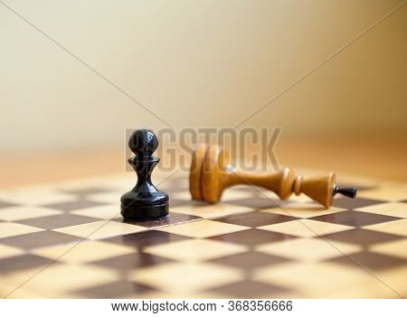 Pawn Wins A Victory Over The King. Wooden Chess Pieces On The Chessboard. Chess Game.