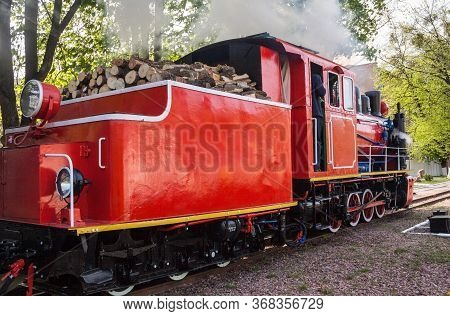 Old Steam Locomotive Blowing Off The Steam Out Of The Whistle. Tender Filled With Wood.