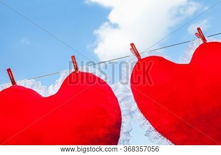 Two Red Heart Shaped Cushions (pillows) Hanged On The Clothes Line And Fastened By The Clothes Pegs