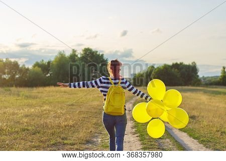 Happy Teenager Girl With Yellow Balloons And Backpack Running And Jumping Along Country Road In Summ