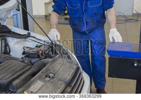 Car Repair At A Service Station. A Professional Mechanic Adjusts The Headlights Of The Car. Adjustin