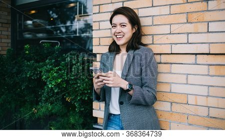 Optimistic And Jovial Female Millennial With Smartphone
