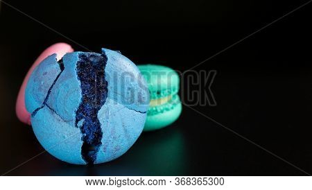 Blue Broken Macaron, Turquoise And Pink Macarons On A Black Background With Copy Space / Place For T