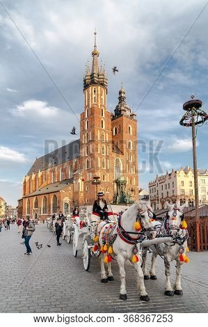 Krakow, Poland - April 24, 2019: Old-fashionedly Dressed Carriers In Carriages With Decorated Horses