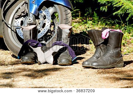Pair of boots next to motorcycle in closeup poster